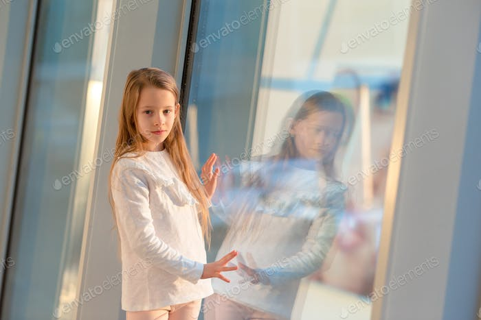 Little girl in airport near big window while wait for boarding