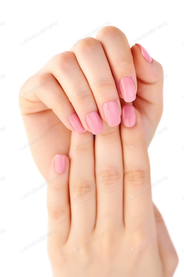 Closeup of hands of a young woman with pink manicure on nails is