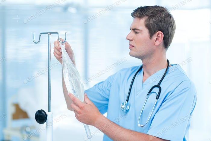 Doctor examining intravenous drip in hospital
