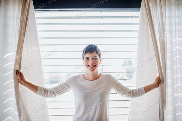 Portrait of young woman standing by window indoors at home, holding curtains.