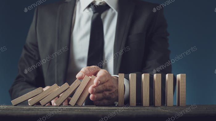 Business executive stopping collapsing dominos with his hand