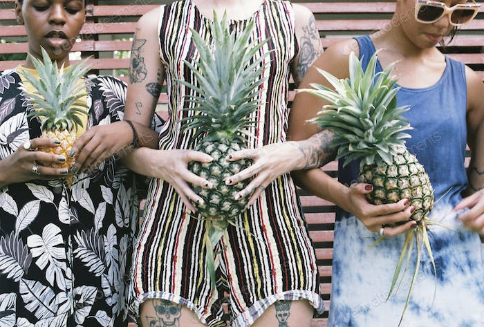 Group of diverse women standing holding pineapple together