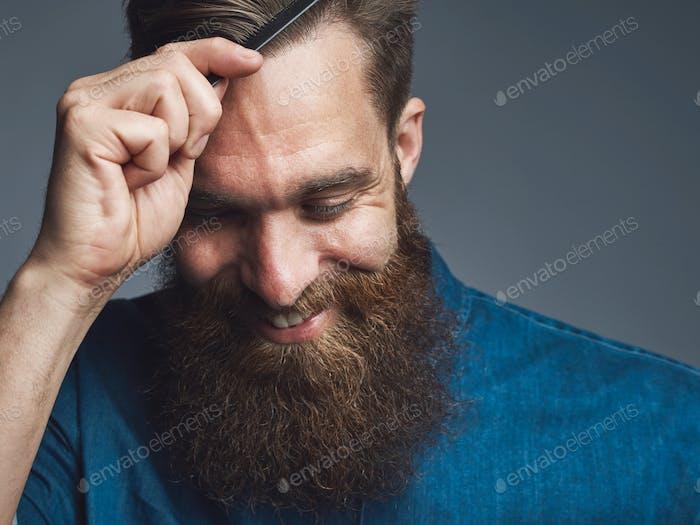 Happy bearded man combing his hair