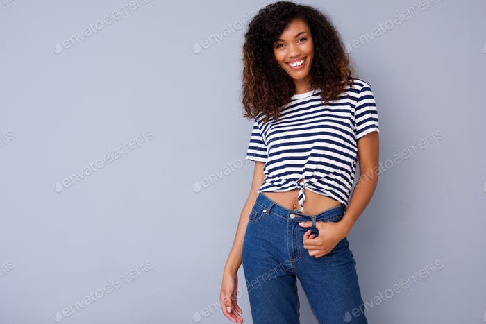 happy young woman smiling in striped shirt against gray background