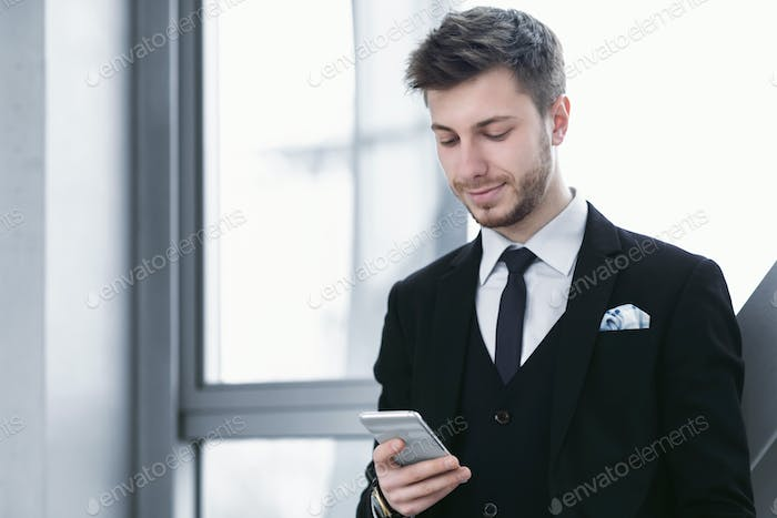 Smiling man holding and looking at phone