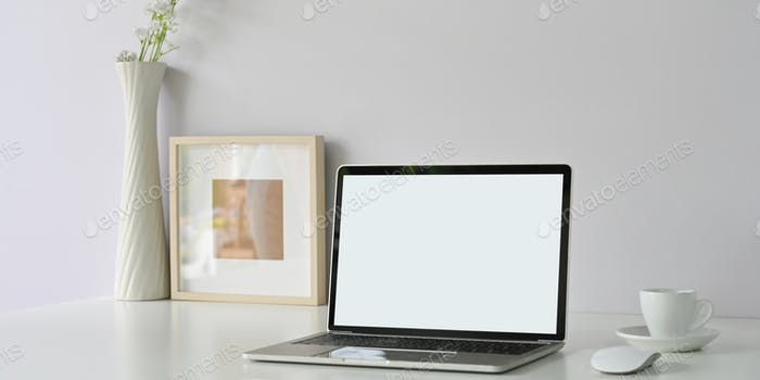 An orderly workspace is surrounding by a white blank screen computer laptop.