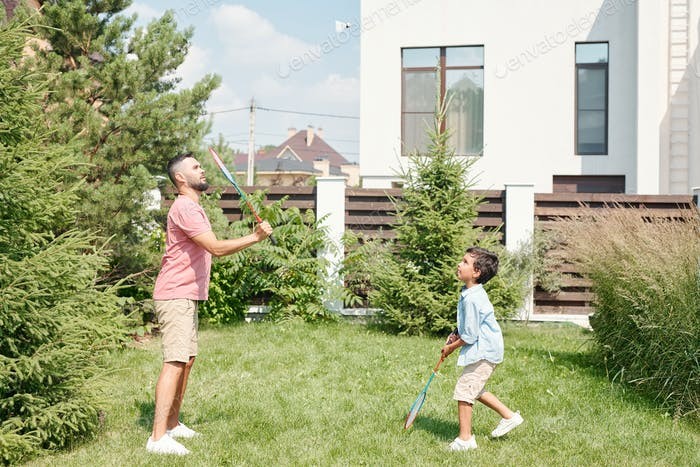 Man And Boy Playing Badminton