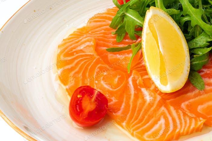 Salmon carpaccio served with lemon and arugula