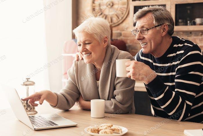 Retired couple browsing on laptop, enjoying tea at kitchen