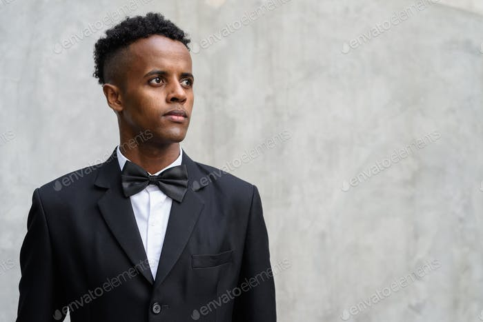 Young handsome African businessman wearing suit against concrete