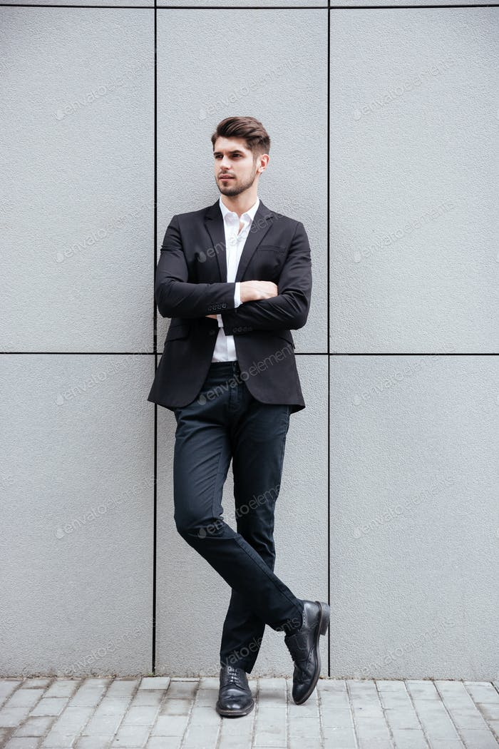 Confident young businessman standing with arms crossed