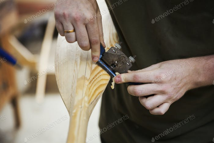 Close up of person working in a boat-builder's workshop, working on a wooden oar.