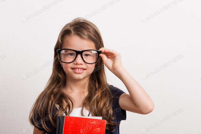 Portrait of a small girl with big eyeglasses in studio on a white background.