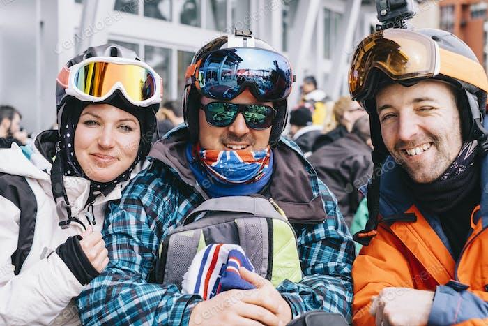 Drei Personen, eine junge Frau und zwei Männer in Skiausrüstung, hintereinander Im Skiurlaub.