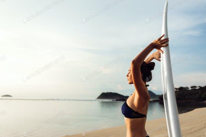 young sexy bikini girl or beautiful woman holding white surfboard