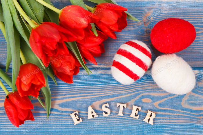Inscription Easter, red tulips and eggs wrapped woolen string on boards, festive decoration