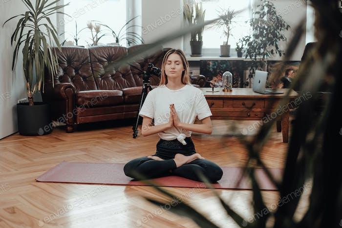Fitness-Frau meditiert im ruhigen und modernen Wohnzimmer