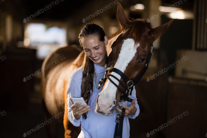 Female vet using mobile phone while standing by horse