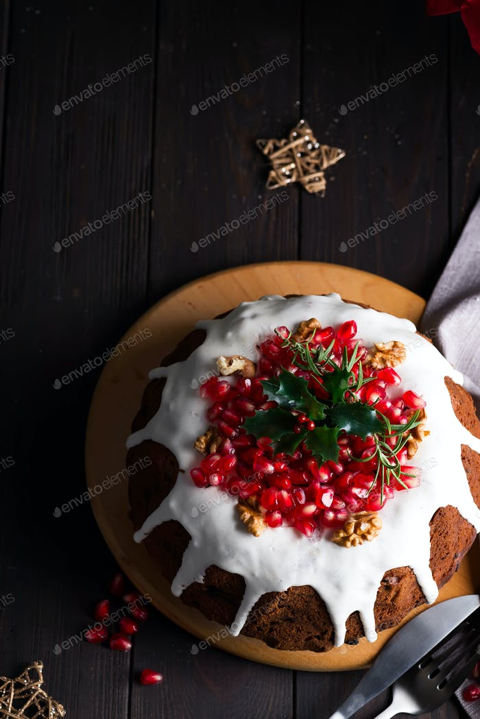 Christmas homebaked chocolate cake decorated with white icing and pomegranate kernels on a wooden
