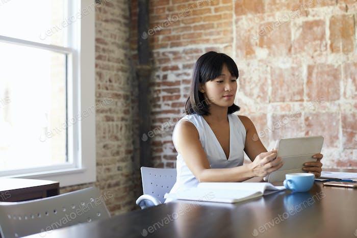 Businesswoman Working On Digital Tablet In Boardroom