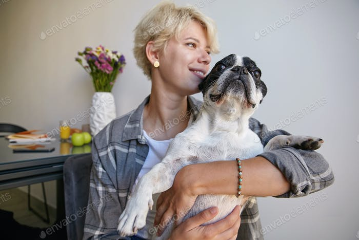 Close-up portrait of happy french bulldog looking at camera and beautiful blond female