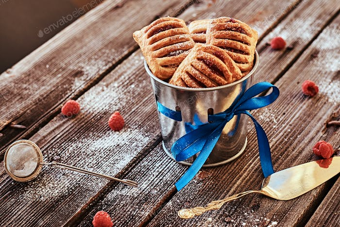 Puff pastry with jam in a bucket decorated with a blue ribbon on wooden boards with raspberries.