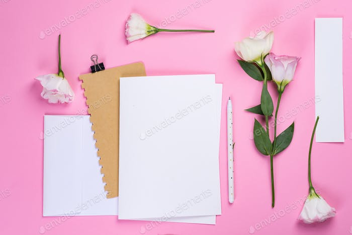 Flowers composition. Paper blank and notebook with eustoma pink flowers on pink background. Flat lay