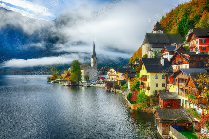 Foggy autumnal sunrise at famous Hallstatt lakeside town reflect