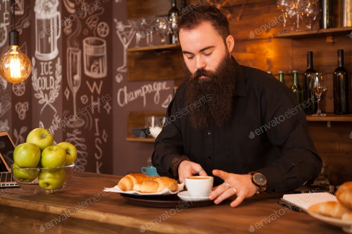Handsome barman behind a bar with a prepared coffee