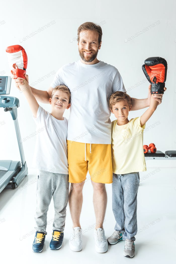 happy father standing with sons in boxing gloves raising hands after sparring
