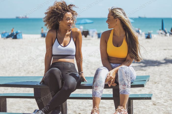Lounging girlfriends in sportswear on beach