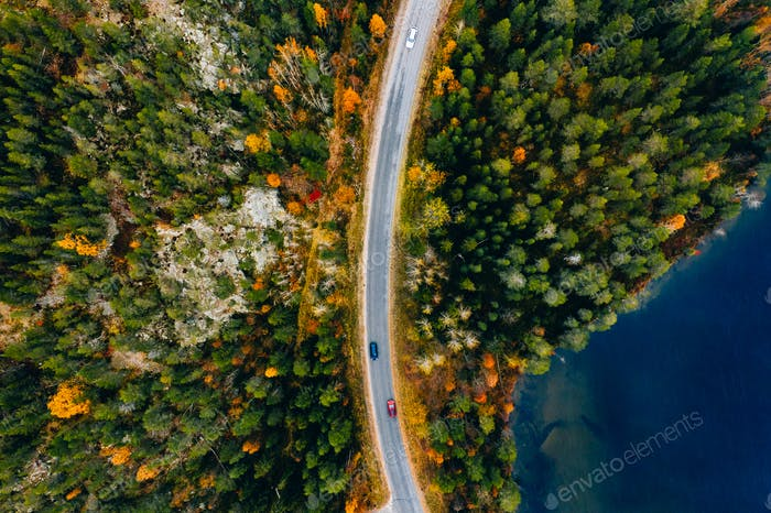 Aerial view of road and colorful autumn forest with blue lakes in Finland.
