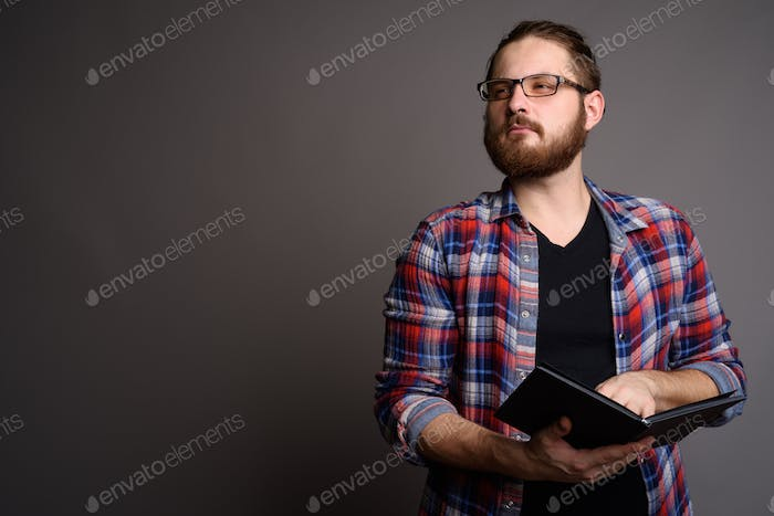 Young bearded man wearing checked shirt against gray background