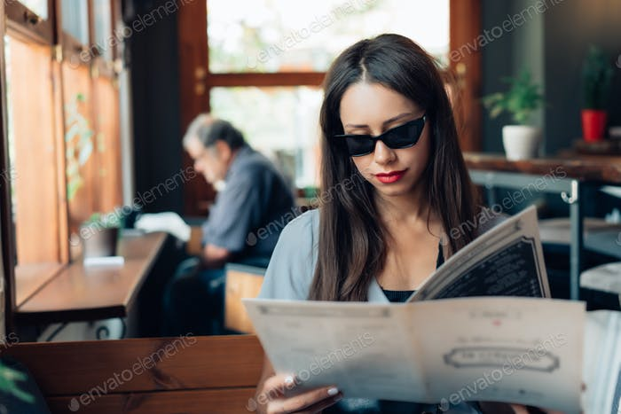 Attractive woman in sunglasses is sitting in a restaurant