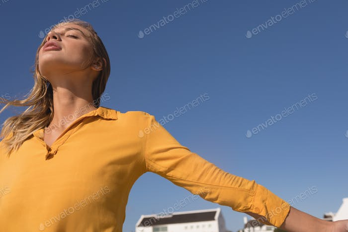 Low angle view of young woman standing with arms outstretched on the beach