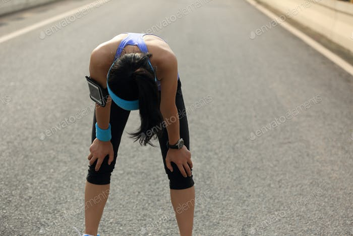 Tired woman runner have a break on road