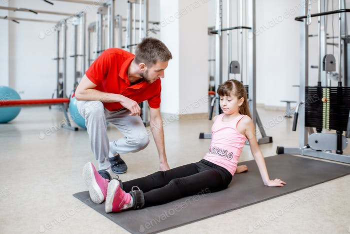 Trainer with young girl at the rehabilitation gym