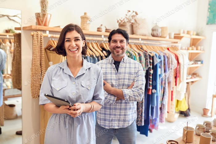 Portrait Of Male And Female Owners Of Fashion Store Checking Stock With Digital Tablet