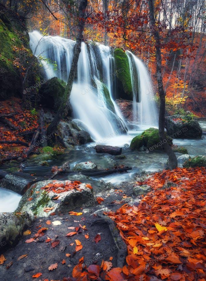 Wasserfall am Bergfluss im Herbstwald bei Sonnenuntergang.