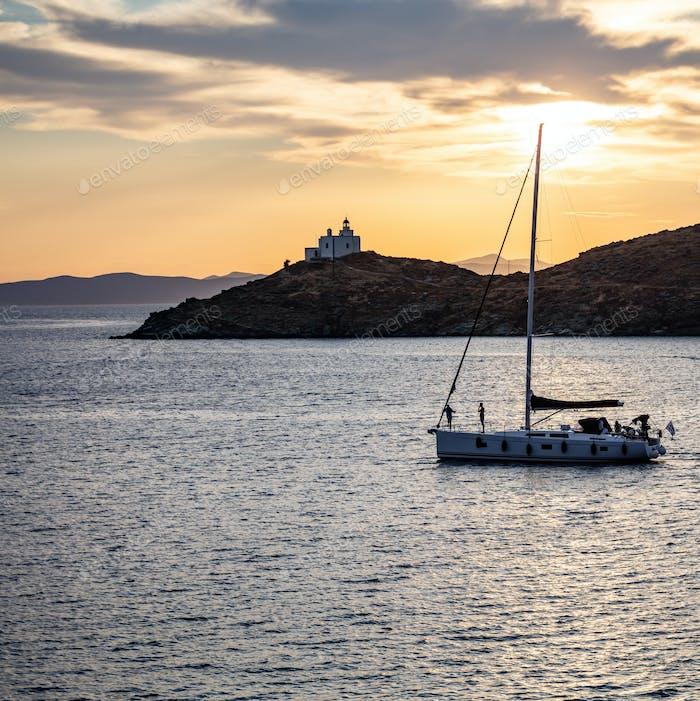 Sailing at sunset, Mediterranean sea. Lighthouse at Kea island, Greece.