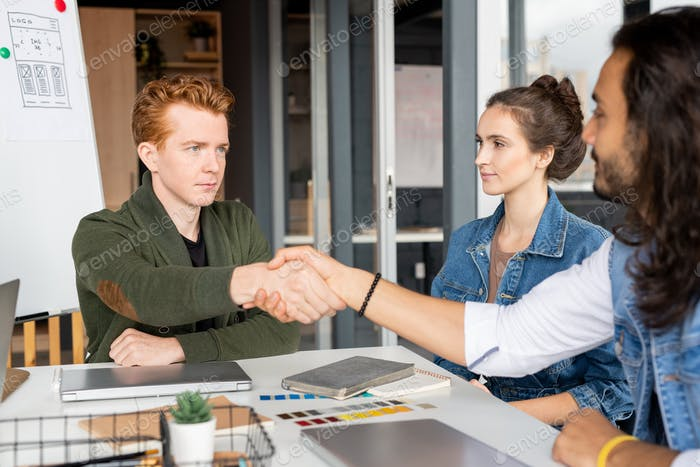 Young serious businessman of Caucasian ethnicity shaking hand of colleague