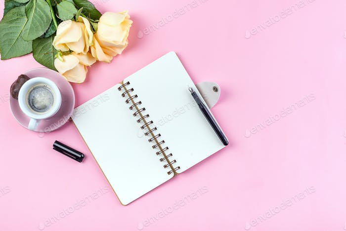 Morning coffee mug for breakfast, empty notebook, pencil and rose on pink table top view . Woman