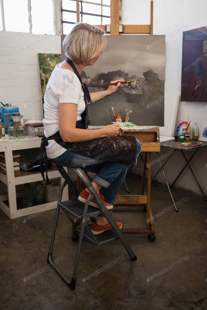 Woman painting on canvas in drawing class