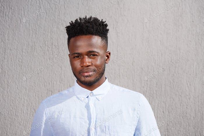 gut aussehende junge afrikaner Mann mit Bart stehend suchen ernst
