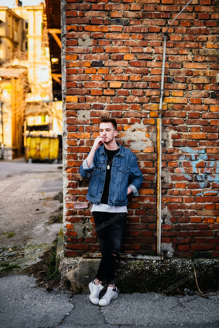 Young man in front of brick wall smoking cigarette