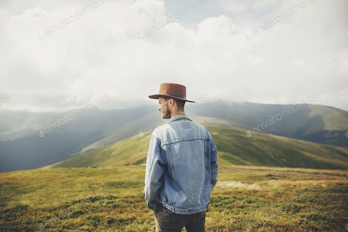 stylish traveler man in hat standing on top of sunny mountains in clouds