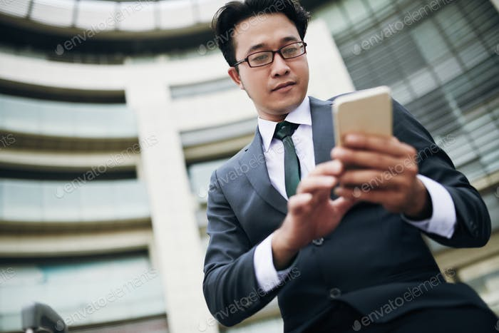 Businessman texting on smartphone