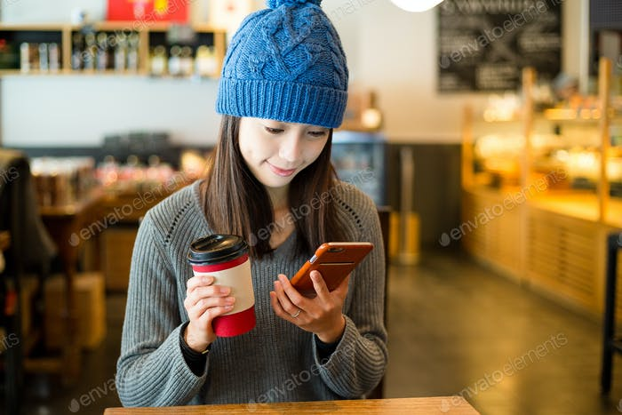 Woman enjoy her morning coffee with cellphone