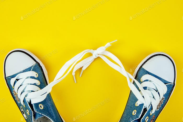 Blue female or male sneakers on yellow paper background