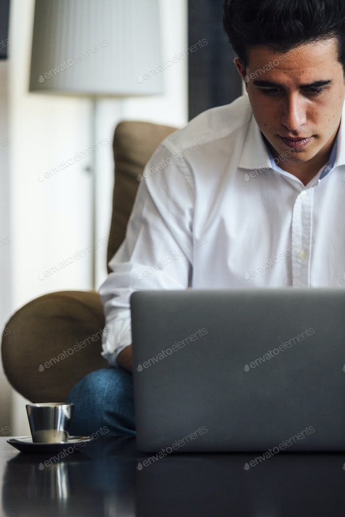 Serious young man working on laptop